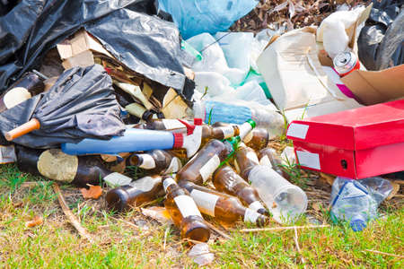 Foto de Illegal dumping with bottles, boxes and plastic bags abandoned in nature - Imagen libre de derechos