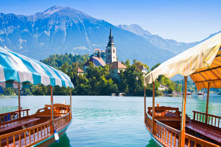 Foto de Typical wooden boats, in slovenian call Pletna, in the Lake Bled, the most famous lake in Slovenia with the island of the church (Europe - Slovenia)  - Imagen libre de derechos