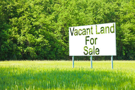 Foto de Advertising billboard immersed in a rural scene with Vacant Land for Sale written on it - image with copy space - Imagen libre de derechos