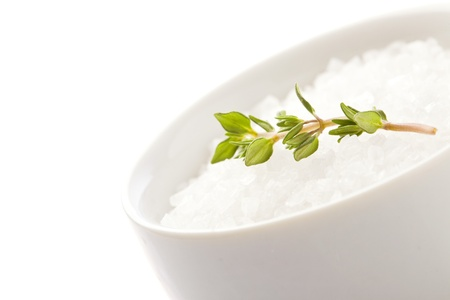 photo of white raw sea salt with parsley on white isolated background