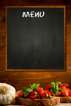 photo of blackboard with bruschetta appetizer background on wooden wall