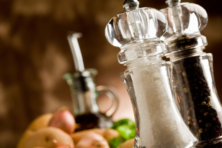 photo of salt and pepper mill with ingredients arround on wooden table