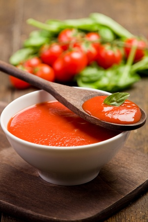fresh red tomato sauce with basil leaf and wooden spoon