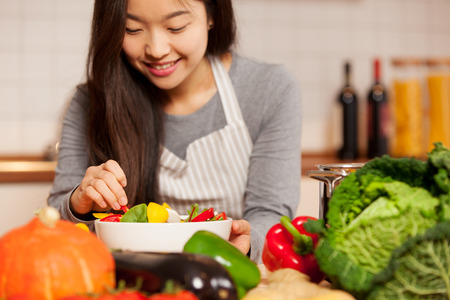 Photo pour asian young woman composing a colorful salad at home in the kitchen - image libre de droit
