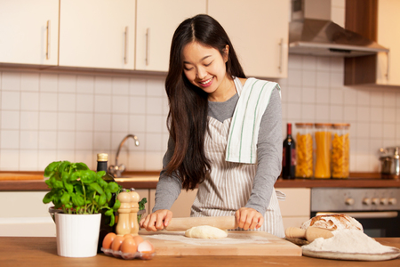Photo for Asian smiling woman is baking bread in her home kitchen - Royalty Free Image