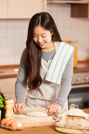 Photo for Asian woman is baking bread in her home kitchen - Royalty Free Image