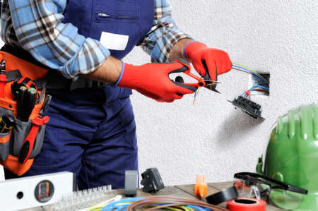 Foto de Electrician with hands protected by gloves and insulated tools works respecting the safety regulations in a residential electrical installation. - Imagen libre de derechos