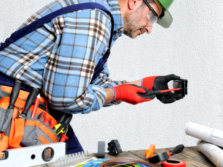 Photo for Electrician with hands protected by gloves and insulated tools works respecting the safety regulations in a residential electrical installation. - Royalty Free Image