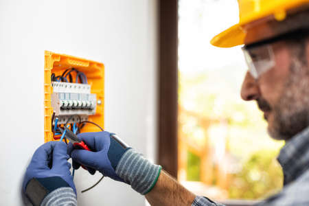 Photo pour Electrician at work on an electrical panel protected by helmet, safety goggles and gloves; wear the surgical mask to prevent the spread of Coronavirus. Construction industry. Covid-19 Prevention. - image libre de droit
