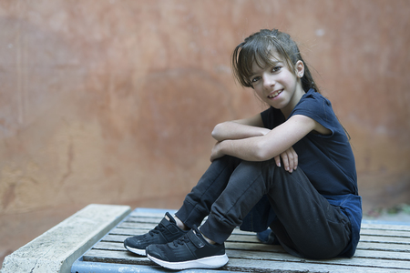 Foto de 10 year old girl sitting on a wooden bench looking at the camera with a smile. - Imagen libre de derechos