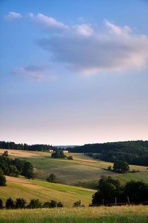 Foto de Beautiful evening landscape in the Spessart area in Germany with clouds in the blue sky and agricultural fields - Imagen libre de derechos
