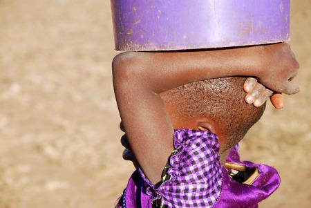 Foto de An African child with a bucket of water - Pomerini - Tanzania - Africa - A little African girl carries on his head a bucket of water - Imagen libre de derechos