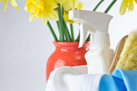 Horizontal shot of cleaning items in foreground with vase of daffodils in background to indicate Spring time.