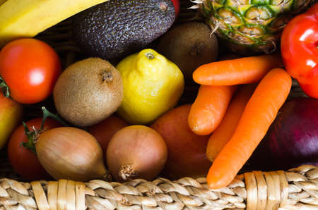 Overhead shot of a basket crammed with raw, fresh, colourful fruit and vegetables.  Landscape orientation.