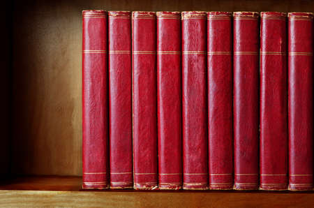A row of old, battered, matching encyclopaedias (circa 1950s) lined up on a shelf, with titles removed to leave blank spines. Red leather effect with gold striped trims. Shelf has been darkened artificially to give impression of age.