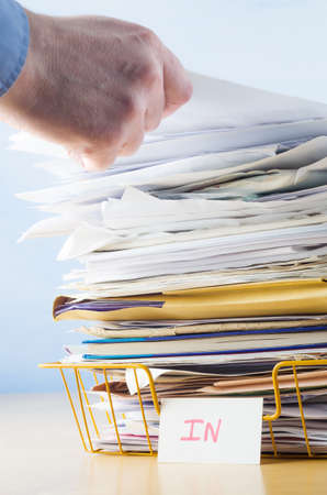 Photo for Business image of a male hand with blue shirt cuff visible, adding or removing document from tall pile in overflowing office In tray. - Royalty Free Image