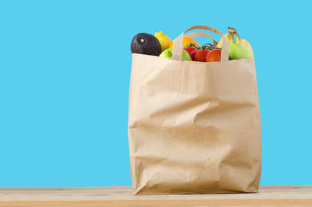 Photo pour A brown paper shopping bag, filled to the top with varieties of fruit, on a light wood surface.  Isolated on a turquoise blue background. - image libre de droit