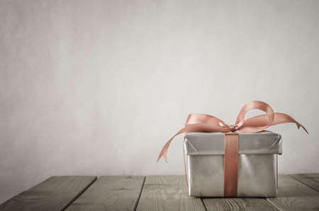 Foto de A gift box with closed lid, wrapped in silver paper and tied to a bow with a satin ribbon.  Placed on a weathered old wooden table with copy space behind and above. - Imagen libre de derechos