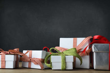 Photo for A variety of Christmas gifts in an untidy row extending beyond each side of the frame.  Placed on a desk with blackboard background. - Royalty Free Image