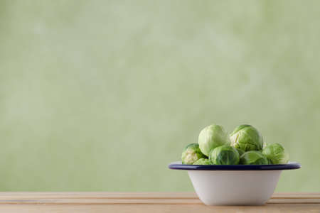 Enamel cooking tin filled with fresh, raw brussel sprouts on light wood plank table.  Green background provides copy space.