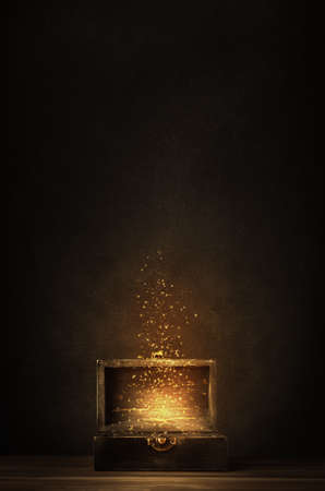 Photo pour Glowing golden sparkles and stars rising from an old, opened wooden treasure chest. Darkly lit on a planked surface with black chalkboard background. - image libre de droit