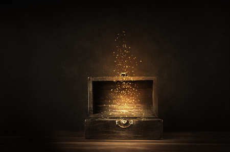 Foto de Glowing golden sparkles and stars rising from an old, opened wooden treasure chest. Darkly lit on a planked surface with black chalkboard background. - Imagen libre de derechos