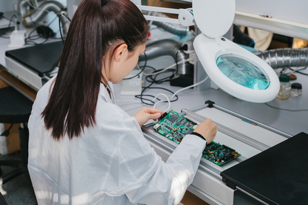 Foto de Beautiful female computer expert professional technician examining board computer in a laboratory in a factory. Technical support. - Imagen libre de derechos