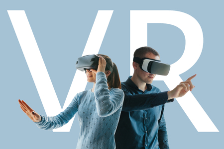 Foto de A young man and a young woman in glasses of virtual reality. The concept of modern technologies and technologies of the future. VR glasses - Imagen libre de derechos