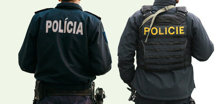 Foto de Isolated on white background a set of policemen with their backs with special clothing with the inscription Police on one of them in the Czech language and on the other in Portuguese and Slovak languages - Imagen libre de derechos