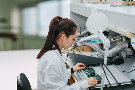 Foto de A female technician checks a computer board in a factory. Professional occupation. Highly qualified specialist in the field of assembly of computers or computer technology. - Imagen libre de derechos