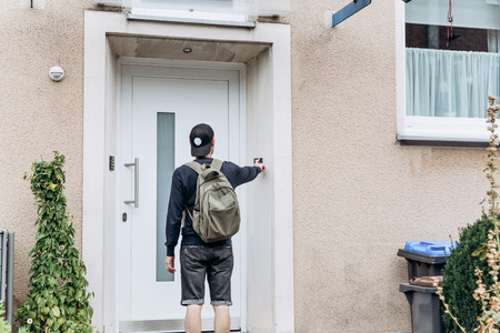 Foto de The tourist rings the doorbell to check in to the room he has booked or the student with the backpack returns home after classes at the institute or on vacation. - Imagen libre de derechos