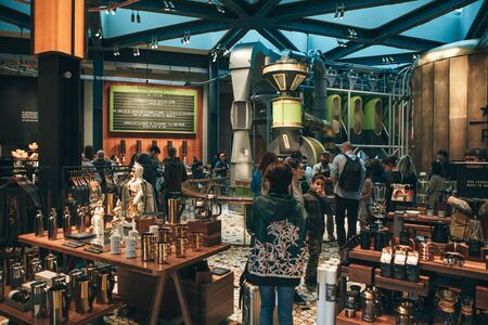 Foto de Italy, Milan, May 30, 2019: People, tourists and coffee lovers at Starbucks Reserve in Milan. The interior of the coffee shop. - Imagen libre de derechos