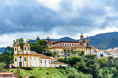Photo pour Ancient historical churches among the houses and streets of Ouro Preto city in Minas Gerais with hills and clouds in the background - image libre de droit