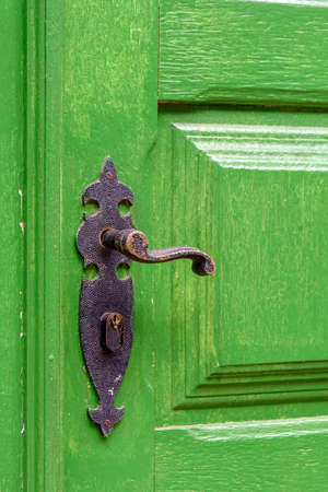 Photo pour Old and aged green wooden door and door handle in the city of Ouro Preto, Minas Gerais with its rusty metal part. - image libre de droit