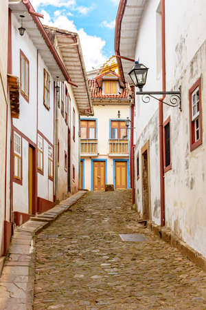 Photo pour Facade of old houses built in colonial architecture with their balconies, roofs, colorful details and cobblestone street in the historical city of Ouro Preto in Minas Gerais. - image libre de droit