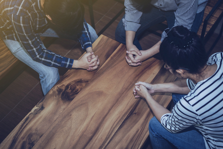 Photo pour Christian people prays together around wooden table. prayer meeting small group concept. - image libre de droit