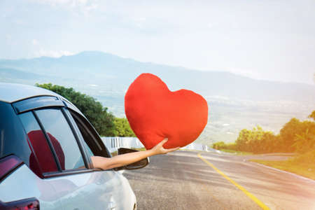 Photo pour Relaxed happy traveler, Young beatiful asian gilr holding big red heart and Reach out of the car at sunset and beautiful view with mountain road background. - image libre de droit
