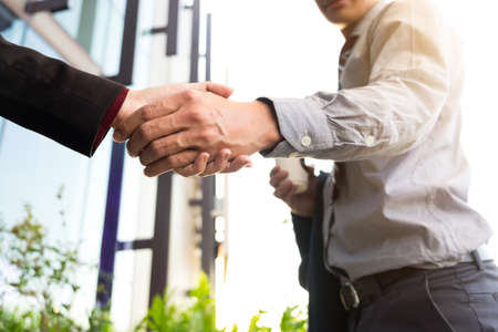Happy smiling business man shaking hands after a deal finishing up a meeting, business outdoors concept.