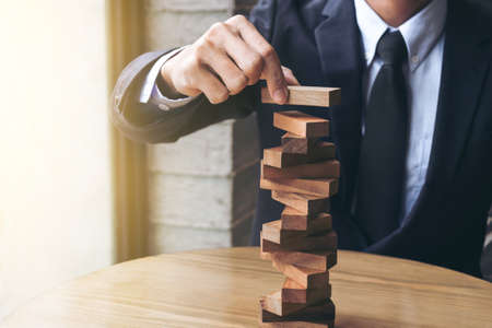 Photo pour Alternative risk concept, plan and strategy in business, Risk To Make Buiness Growth Concept With Wooden Blocks, Images of hand of businesspeople placing and pulling wood block on the tower. - image libre de droit