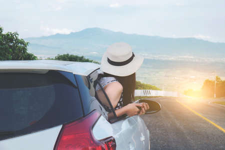 Foto de Relaxed happy traveler, Young beatiful asian gilr wearing white Hat weave using smart phone and Reach out of the car at sunset and beautiful view with mountain road background. - Imagen libre de derechos