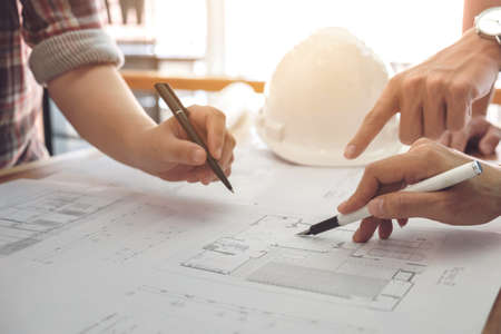 Photo pour Image of engineer or architectural project, Close up of Architects engineer's hands drawing plan on BluePrint and discussing to partner with Engineering tools on workplace, Construction concept. - image libre de droit