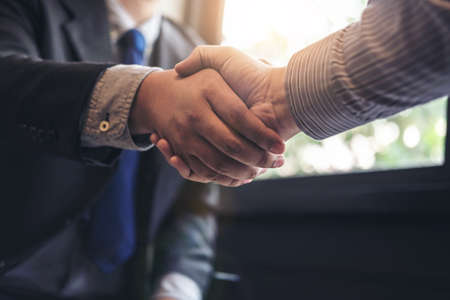Photo for Two business men shaking hands during a meeting to sign agreement and become a business partner, enterprises, companies, confident, success dealing, contract between their firms. - Royalty Free Image