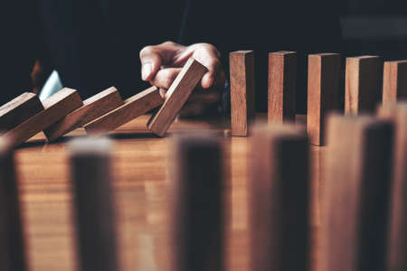 Foto de Close up of businessman hand Stopping Falling wooden Dominoes effect from continuous toppled or risk, strategy and successful intervention concept for business. - Imagen libre de derechos