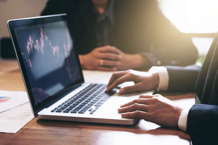 Photo pour Business team two colleagues working with computer, digital tablet, discussing and analysis graph stock market trading with stock chart data, financial and investment concept. - image libre de droit