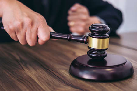 Foto de Male lawyer or judge hand's striking the gavel on sounding block, working at courtroom, Law and justice concept. - Imagen libre de derechos