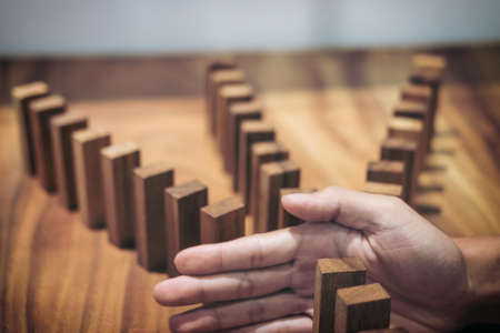 Photo for Risk and strategy in business, Close up of businessman hand stopping wooden block between three way from falling in the line of domino. - Royalty Free Image