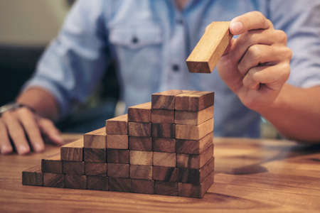 Foto de Alternative risk concept, plan and strategy in business, Risk To Make Business Growth Concept With Wooden Blocks, hand of man has piling up and stacking a wooden block. - Imagen libre de derechos