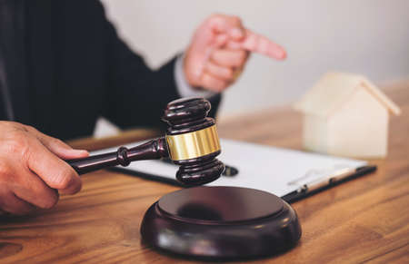 Foto de Male lawyer or judge hand's striking the gavel on sounding block, working at courtroom for decide home insurance, Law and justice concept, Settle a house dealing lawsuit. - Imagen libre de derechos
