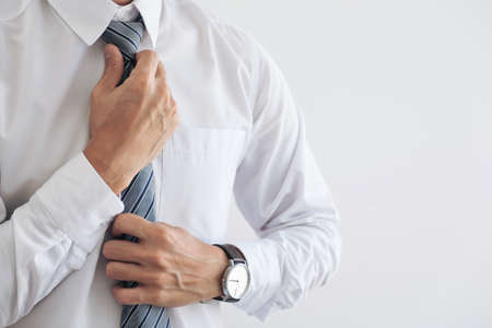 Photo for Close up of Young attractive businessman wears a gray tie and adjusting tie. - Royalty Free Image