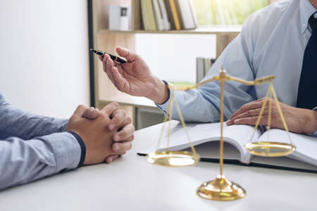 Foto de Judge gavel with scales of justice, Business people and male lawyers discussing contract papers at law firm in office. Concepts of law. - Imagen libre de derechos